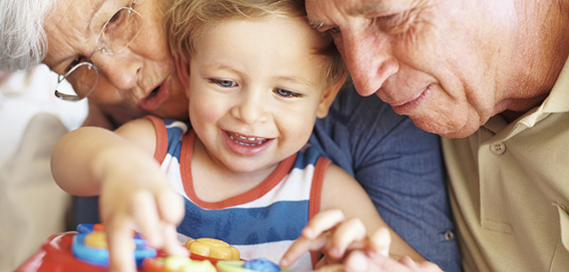 Closeup of boy playing with a toy with his grandparents