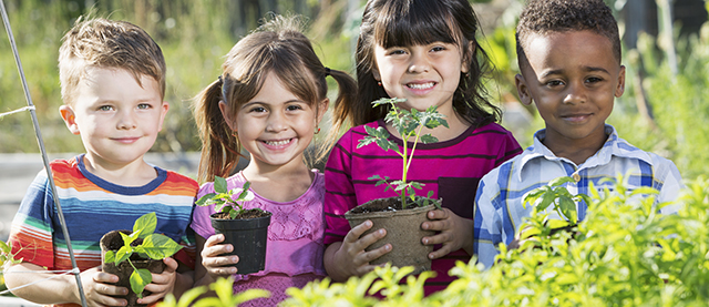Four diverse children in garden holding potted seedlings