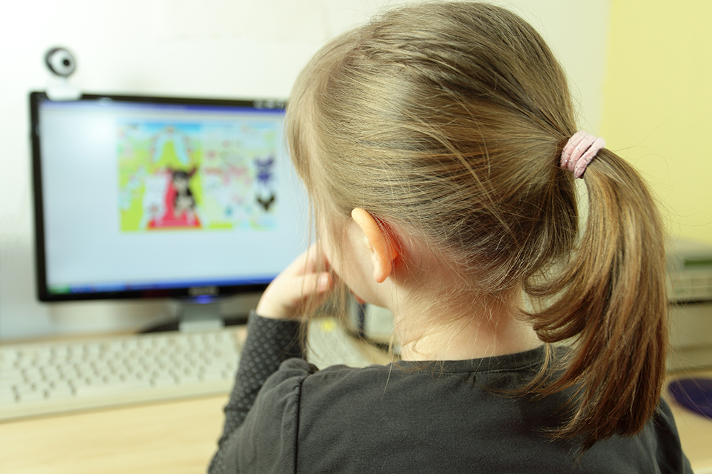 A girl at the age of 6 playing a smart game on the PC and learning new skills.