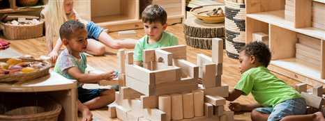 Three little boys playing with blocks and building a structure together