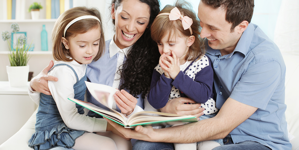 Two girls sitting on their mom and dad's laps while reading a book together