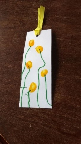 A handmade book mark with painted yellow flowers and a yellow ribbon on the top