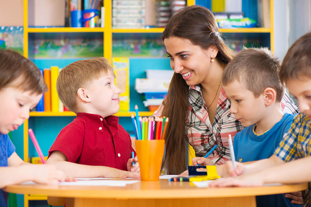 A teacher and a student smiling at each other while the boy colors at a table with his friends