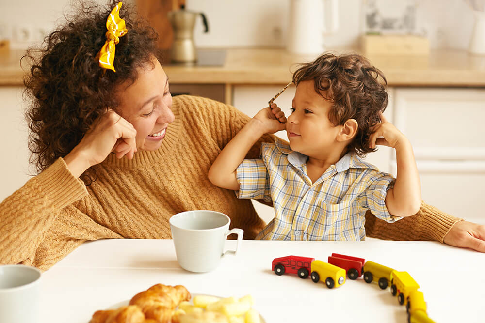 A mom holding her son on her lap at the breakfast table with the boy's toy trains in front of them