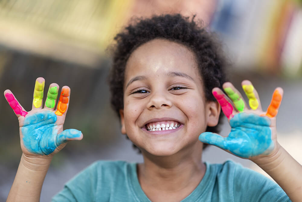 A preschool boy smiling with his colorful painted hands in the air