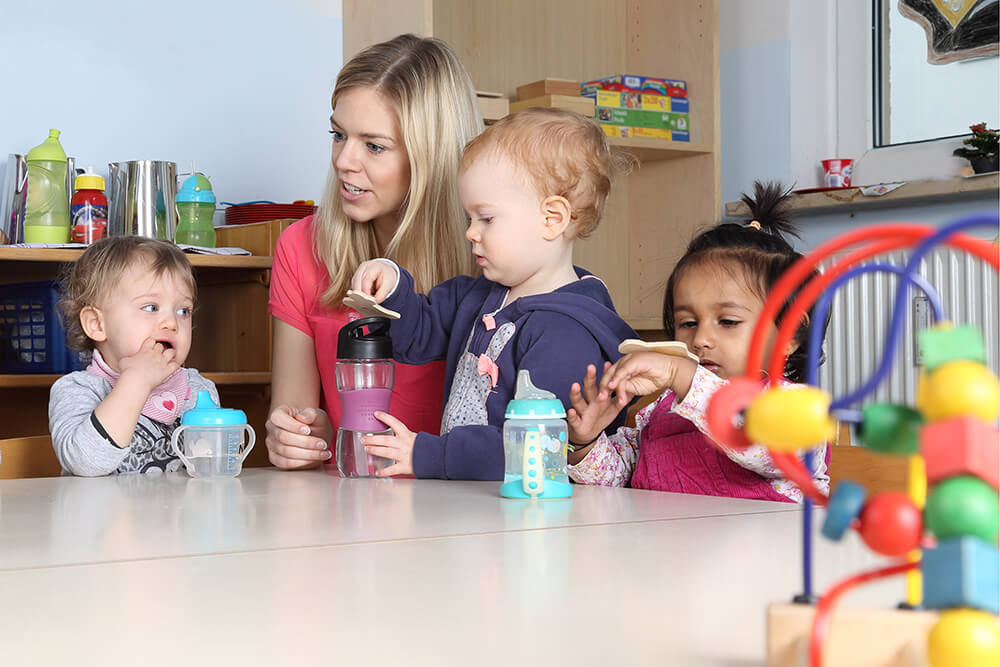 A teacher sits at a table in the classroom with three toddlers during snack time